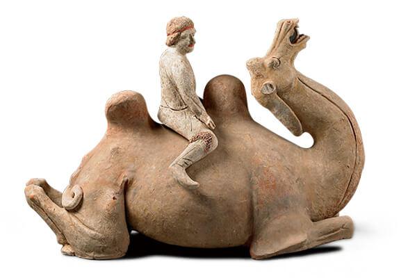 唐代.加彩坐骑骆驼俑+骆驼跪伏在地,背上驮负胡人,表面彩绘斑驳,颇能反映丝路行旅的风尘与辛劳。(图三)