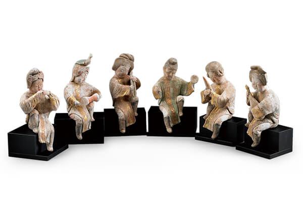 唐代.加彩乐伎俑+乐伎手持乐器,神情十分专注,表面原有彩绘呈现宫廷乐团的演奏盛况。(图五)