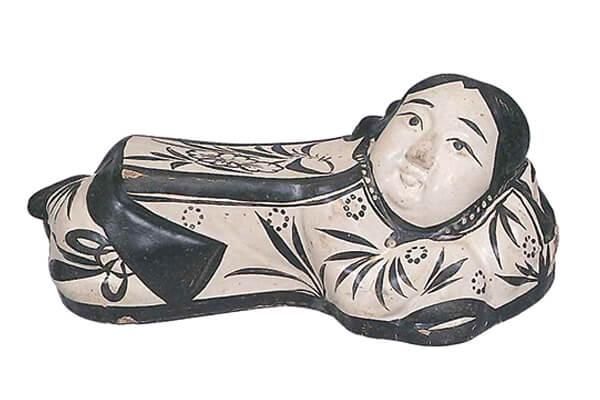 金代.白地铁绘孩童枕+表面先涂白色化妆土,用铁着色剂绘画孩童的五官样貌与衣着,施透明釉后烧成白地黑花装饰。(图四)+图片来源:《中国+磁州窑+出光美术馆》,页37,图54。